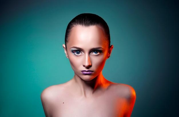 De kunstmake-up van de schoonheid op het gezicht van een vrouwenmeisje