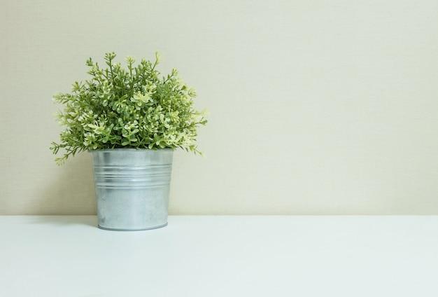 De kunstmatige installatie van de close-up in pot voor verfraait op vage houten witte bureau en muur geweven achtergrond