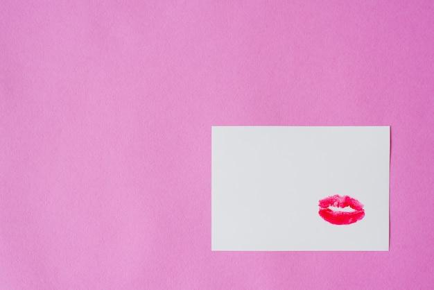 De kusafdruk is gemaakt met rode lippenstift op wit papier met roze achtergrond. kopieer ruimte. valentijnsdag kaart