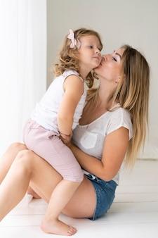 De kussende dochter van de zijaanzichtvrouw op de wang