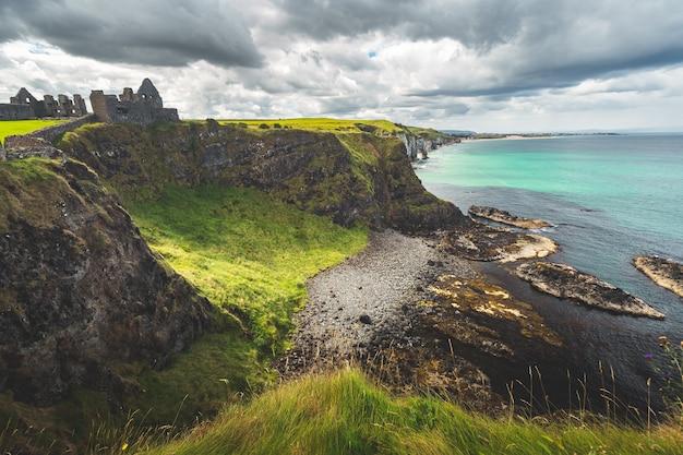 De kustlijn van noord-ierland met dunluce-kasteel in de verte, pittoresk met gras bedekt laagland en