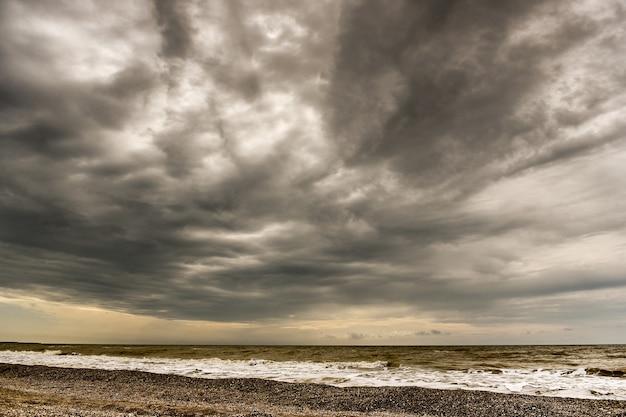 De kustlijn van schelpen op een achtergrond van zee en blauwe lucht
