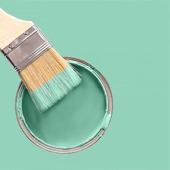 De kwast in de verfkleur van neomunt en het blik met verfkleur neomunt boven neomunt.