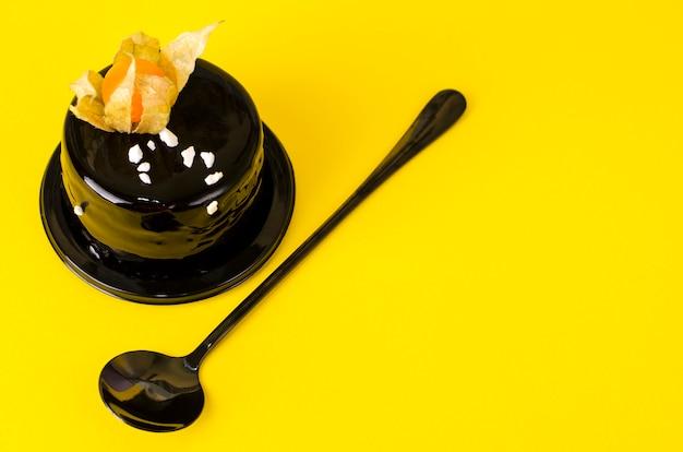 De laagcake van de chocolade met een rijke donkere chocolade die op gele achtergrond berijpt