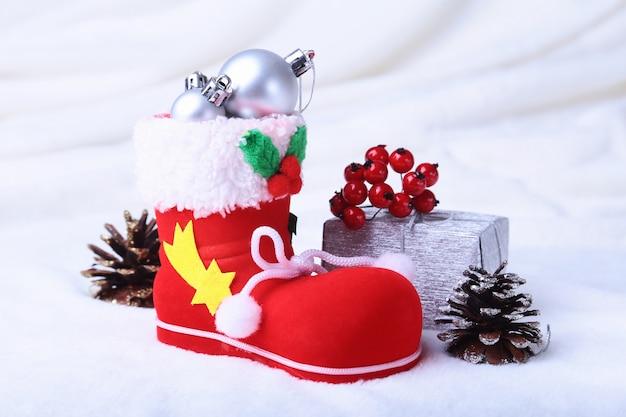 De laars van de rode kerstman met kerstcadeaus op sneeuw. fijne feestdagen samenstelling.