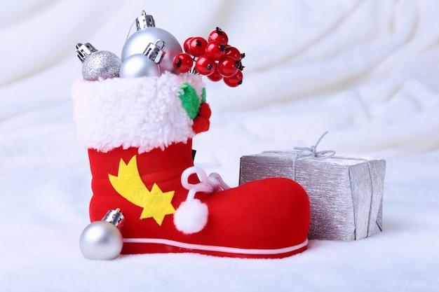 De laars van de rode kerstman met kerstmisgiften op sneeuwachtergrond. fijne feestdagen samenstelling.