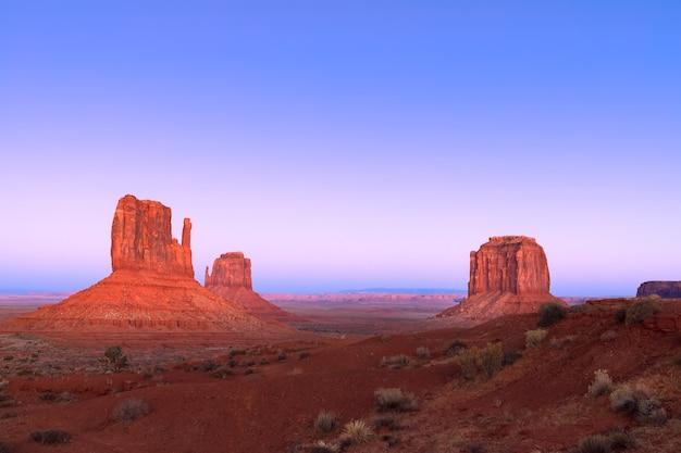 De laatste stralen van de ondergaande zon verlichten de beroemde buttes of monument valley op de grens tussen arizona en utah, vs.