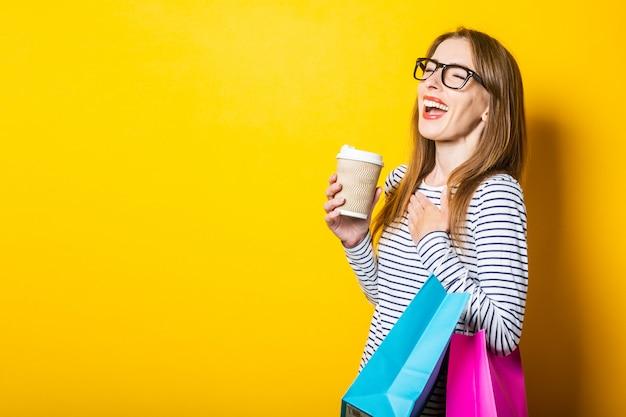 De lachende jonge vrouw verheugt zich met een papieren beker met koffie en tassen op een gele achtergrond