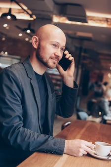 De lachende man in pak spreken op mobiele telefoon, zitten met koffie in café