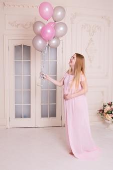 De lachende zwangere vrouw met roze en grijze luchtballons, handen op maag, overhandigt buik.