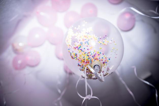 De lage hoekmening van kleurrijk bestrooit in de witte ballon op verjaardagspartij