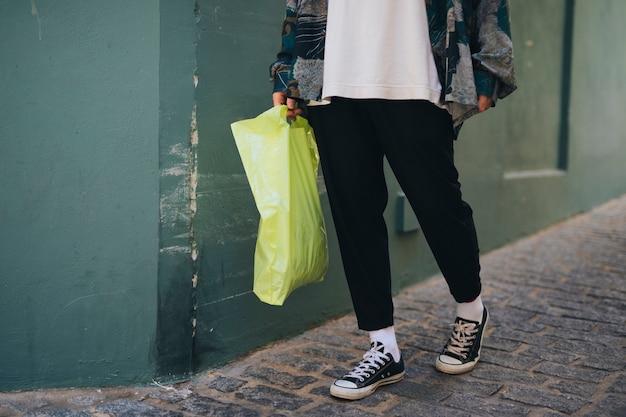 De lage sectie van een mens die zich dichtbij de muur bevinden die groen draagt draagt zak in hand