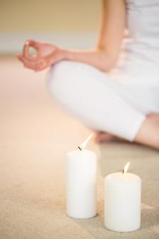 De lage sectie van vrouw in yoga stelt met verlichte kaarsen