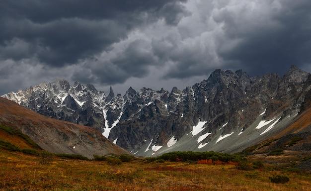 De lage stormachtige wolken raken de top van de besneeuwde berg. somber bewolkt, geweldig landschap met grote rotsen en gletsjer