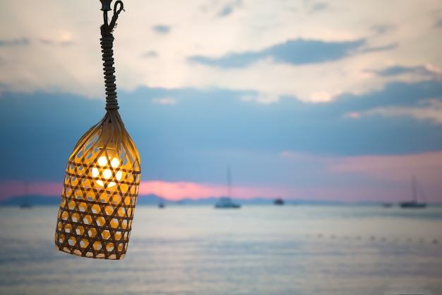 De lamp op de draad vastgebonden met een touw op de achtergrond van het strand binnen schijnt de gloeilamp