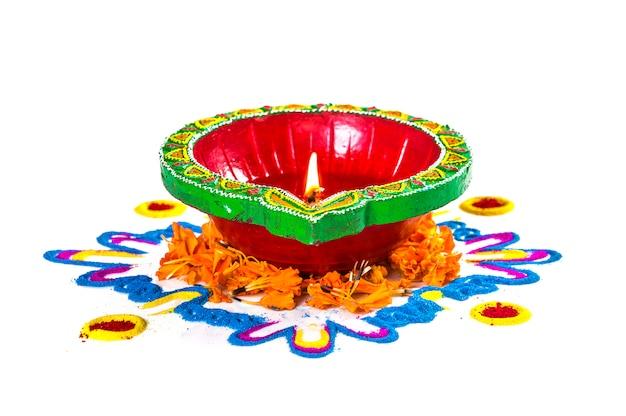 De lamp van kleidya tijdens diwalifestival wordt aangestoken dat. clay diya op rangoli. indian hindu festival of lights genaamd diwali.