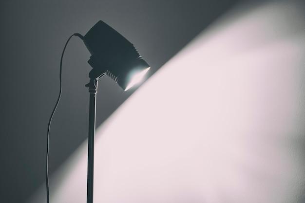 De lamp verlicht de witte muur in de donkere kamer