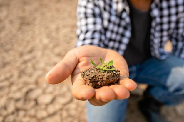 De landbouwer bevindt zich in de droge rivier en kijkt aan leeg water in sukhothai. voor droogte seizoen concept