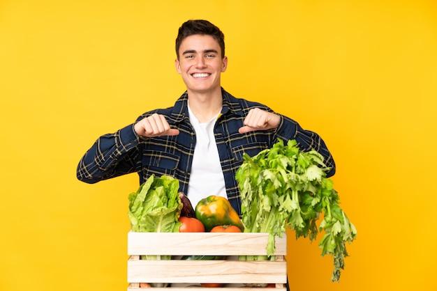 De landbouwersmens van de tiener met vers geplukte groenten in een doos trots en zelfvoldaan