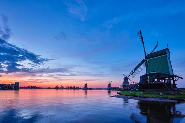 De landelijke scène van nederland - windmolens bij beroemde toeristenplaats zaanse schans in holland op zonsondergang met dramatische hemel. zaandam, nederland
