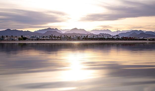 De landschapslucht wordt in de zee weerspiegeld in het ondergaande licht. stadskustlijn met bergen aan de horizon.