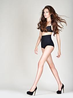 De lange benen van de vrouw op hoge hakken met een perfect lichaam. fahsion model poseert in de studio met zwart slipje