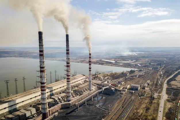 De lange pijpen van elektrische centrale, witte rook op landelijk landschap, meerwater en de blauwe hemel kopiëren ruimteachtergrond.