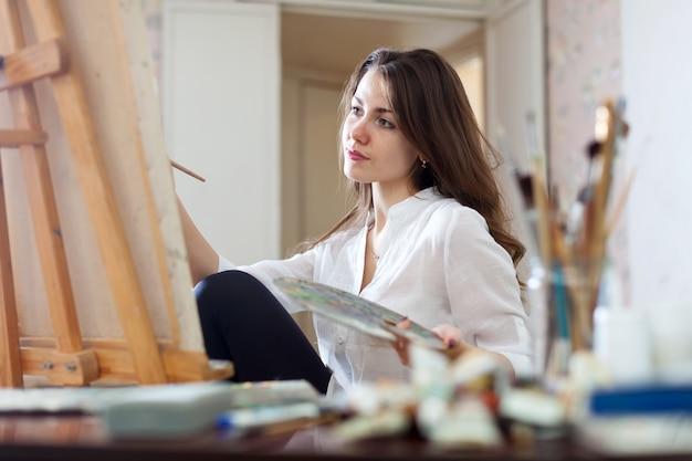 De langharige vrouw schildert beeld op canvas