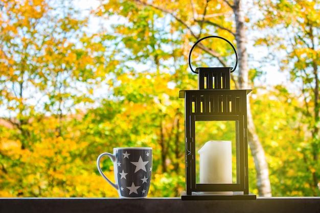 De lantaarn met een kaars en een kopje koffie op een achtergrond van herfstbos