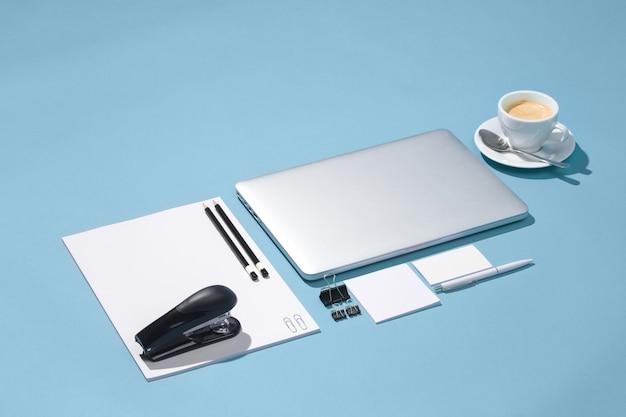 De laptop, pennen, telefoon, notitie met leeg scherm op tafel