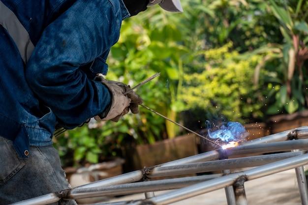 De lasser is het stalen frame aan het lassen. arbeid en industrie werken hard.