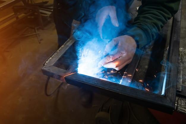 De lasser kookt het frame. de lasser kookt het metaal. de lasser kookt metalen structuren. lassen werkt. vonken, gesmolten metaal