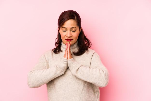 De latijnse vrouw van middelbare leeftijd die op een roze muurholding wordt geïsoleerd dient bidt dichtbij mond in, voelt zeker.