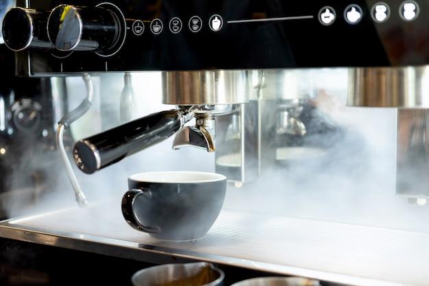 De latte kunst van de koffiekop die op de stoom van de koffiemachinemachine in de koffie van de koffiewinkel wordt geplaatst Premium Foto