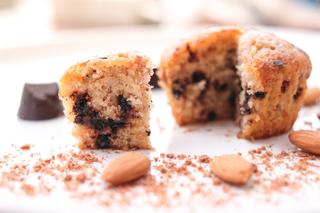 De lava van de muffinchocolade (banaancake) met chocoladeschilfer, amandel en banaangeur op witte plaat voor dessertachtergrond of textuur - eigengemaakt concept.