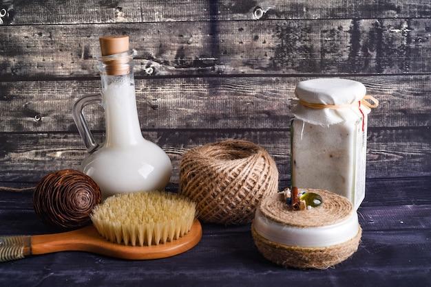 De lay-compositie met lichaamsverzorgingsproducten op donkere houten achtergrond. een potje natuurlijke room, een fles kokos en een borstel om te wassen