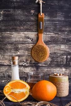 De lay-samenstelling met producten voor lichaamsverzorging. een potje natuurlijke room, een fles kokosolie en een rijpe sinaasappel. kopieer ruimte