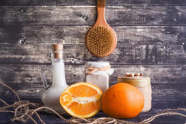 De lay-samenstelling met producten voor lichaamsverzorging. een potje natuurlijke room, een fles kokosolie en een rijpe sinaasappel