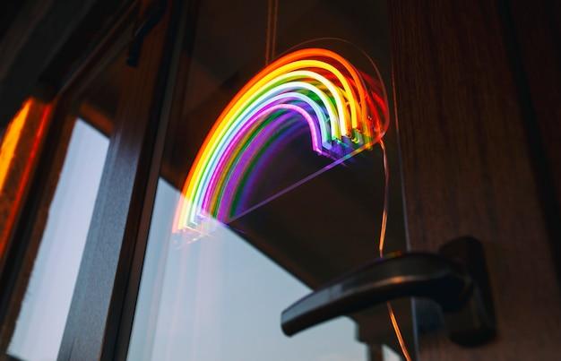 De led-neonregenboog die aan de deuringang in het café hangt