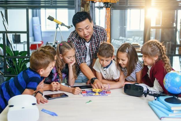 De leerkracht toont een werkend model van een bedradingsschema aan een groep leerlingen op de basisschool.