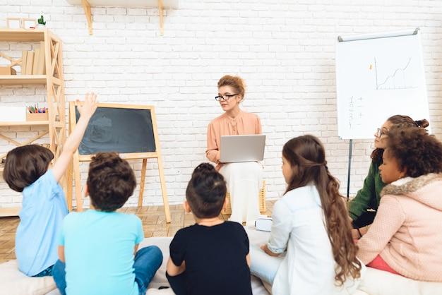 De leerling trekt zijn hand om de vraag van de leraar in een bril te beantwoorden