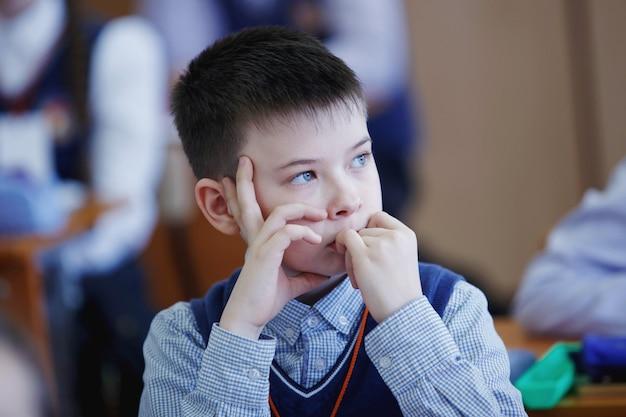 De leerlingen aan de balie denken na en beslissen over de taak in de school. basisonderwijs, opleiding en mensen concept