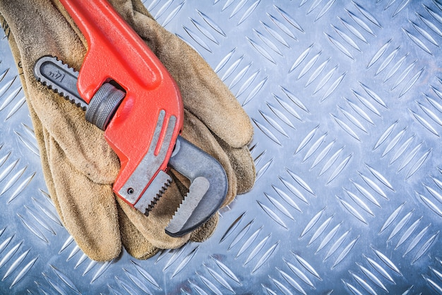 De leerveiligheid gloves de moersleutel van de pijp op gekanaliseerd de bouwconcept van de metaalplaat