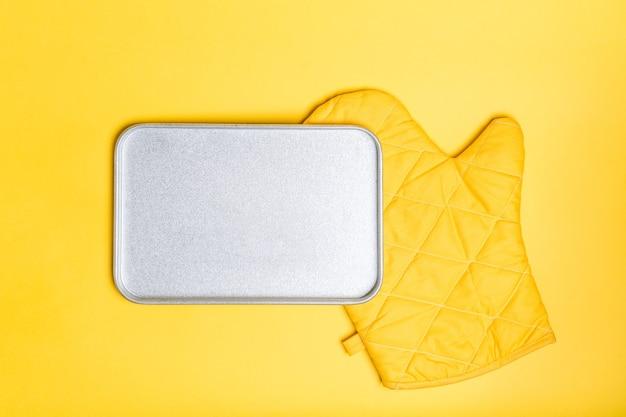De lege bakplaat plaatst over gele ovenhandschoen op gele oppervlakte