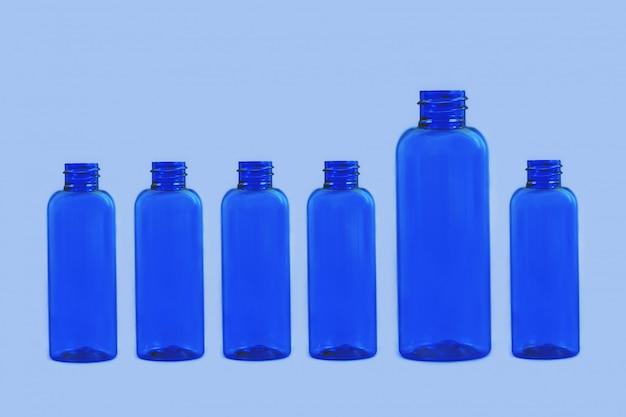 De lege doorzichtige plastic crème potten op blauw.