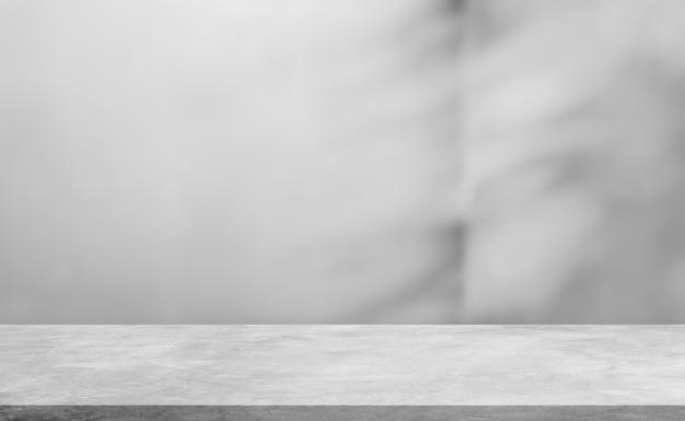 De lege grijze plank van de cementvloer en de vage achtergrond van schaduwbladeren