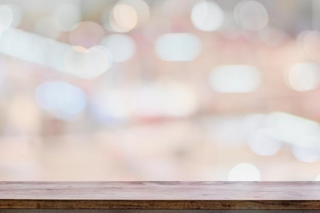 De lege houten teller van de lijstbovenkant op heldere bokeh binnenlandse vage achtergrond