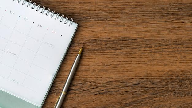 De lege kalender van het bovenaanzicht met een pen op bureau