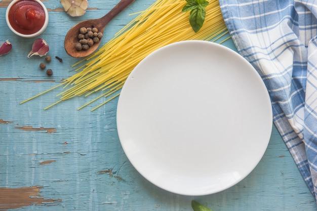 De lege plaat met ingrediënten voor deegwaren met tomaat pakt