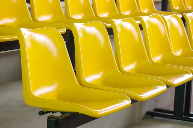 De lege plastic gele zetelsrij bij stadion binnen toont
